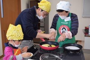 ▲女性部員�に教わりながら焼きりんごケーキを作る親子