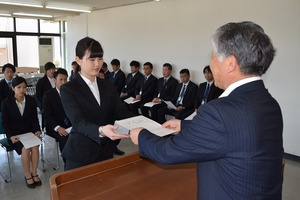 千國組合長(右)から辞令を受け取る新採用職員