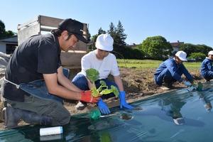 ▲営農指導員�に教わりながら苗を植える生徒
