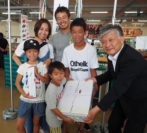 ▲千國組合長(右)から記念品を受け取る野澤さん家族