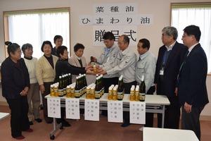 ▲各学校給食センターの所長(右側)に油を手渡すプロジェクトメンバー