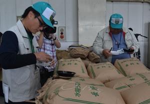 ▲米袋から新米を抜き出し、外見や水分量を確認する検査員