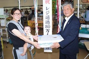 ▲千國組合長から記念品のリンゴを受け取る鈴木さん(左)