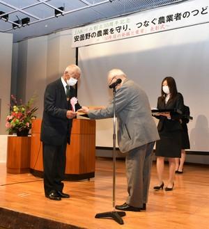 ▲昨年の表彰式で金賞を受賞した西村さん�に記念品を贈る河崎委員長�