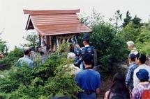 約6時間かけて有明山頂上に到着し、神事を行う参加者。